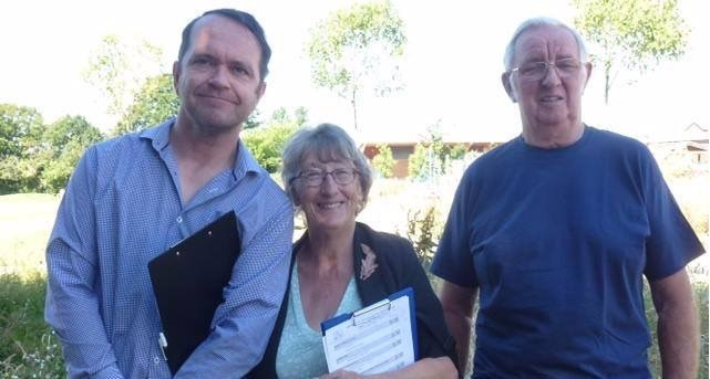 greg burt, keith brown and jean griffin smiling in front of a beautiful garden